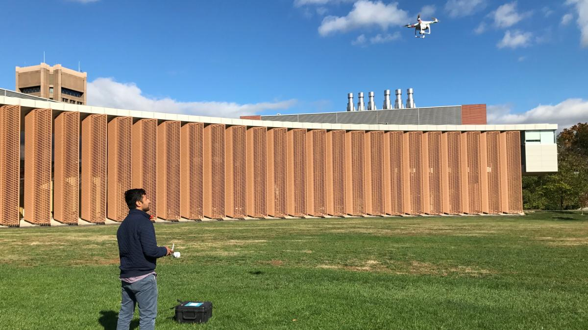 A graduate student tests flight controls of a Parrot quadcopter on Pardee Field.