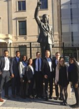 Members of the undergraduate policy task force posing in front of a statue of Nelson Mandela. Photo courtesy of Karl and Sally le Roux.