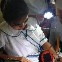 A student studying by the light of her solar lamp, provided by the Solar Library Program