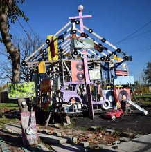 """House of Soul"" — one the original ""inside-out"" houses in the Heidelberg Project — was one of the numerous houses set ablaze in a series of arsons in 2013. The loss of one of Guyton's crucial works was a tragic reminder of Guyton's persistent theme of change and time on the historic Heidelberg Street. The image above captures the reconstructed framework of the ""House of Soul,"" and features Guyton's current project of placing painted clocks throughout the street. (Photo and caption by Alex Quetell, Class of"